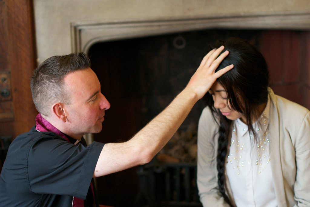 Westminster Youth Chaplain, Fr David Reilly, blessing one of the SPEC volunteer missionaries