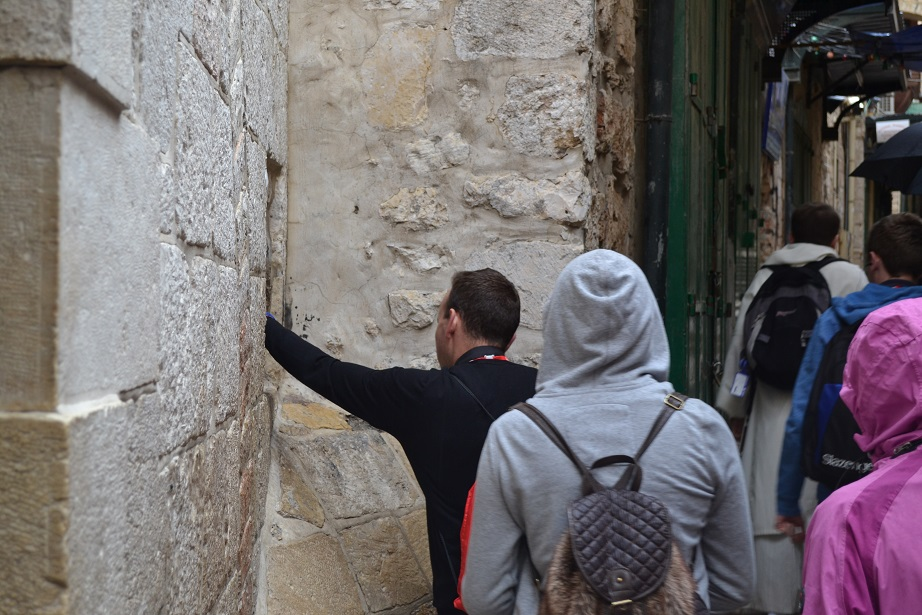 Touching the wall where Jesus leaned on as he carried the cross