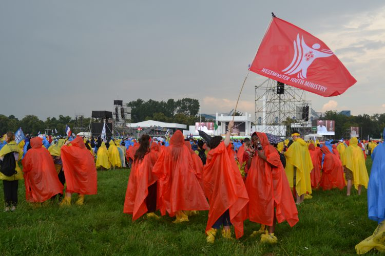 In our ponchos, we waved the flag to make sure everyone knew where to meet up for the Opening Mass (Photo: WYM)