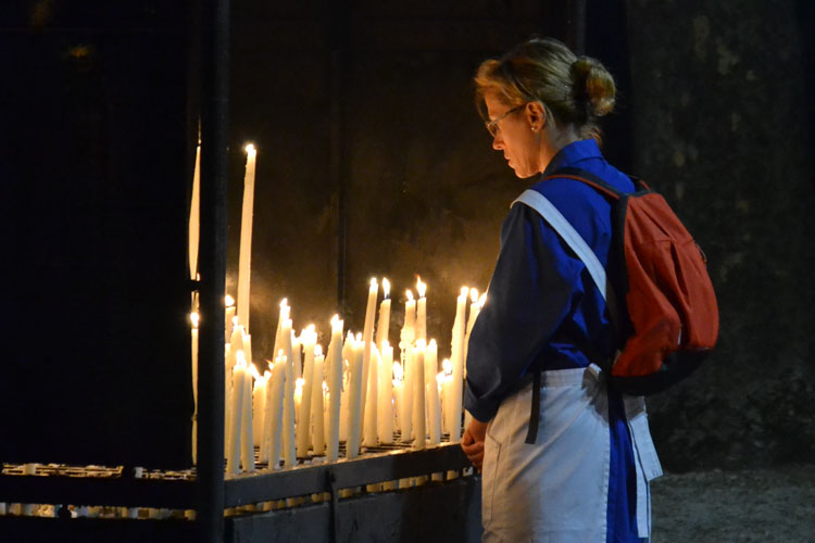 A woman lighting a candle at Lourdes (Photo: WYM)